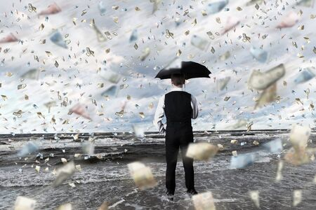money falling: Young businessman standing with umbrella under money rain Stock Photo