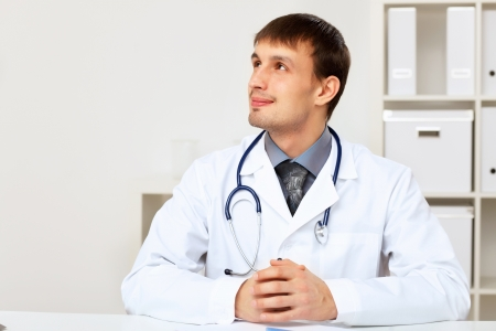 Young male doctor in white uniform at workplace photo