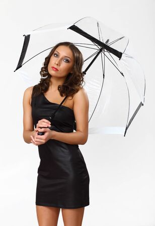 Portrait of young woman with umbrella in studio photo