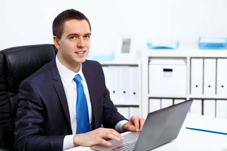 Young manager working with notebook in the office photo
