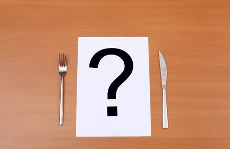 banquet table: Metal knife and fork on the table and question mark