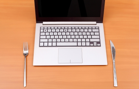 Laptop computer with fork and knife on the table photo