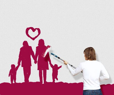 Young man with a paintbrush and family picture on the wall Stock Photo - 14107082