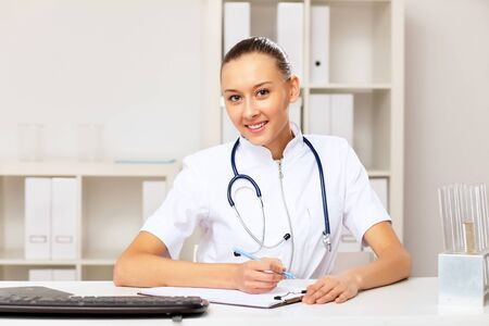 Young female doctor in white uniform at workplace photo