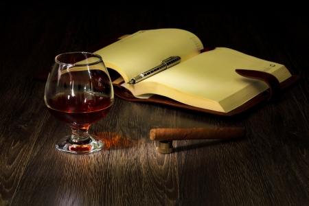 A glass with cognac, cigar and an old book nearby Stock Photo - 14149635