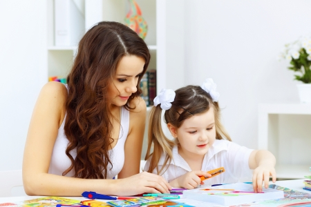 Young mother with little daughter studying at home photo
