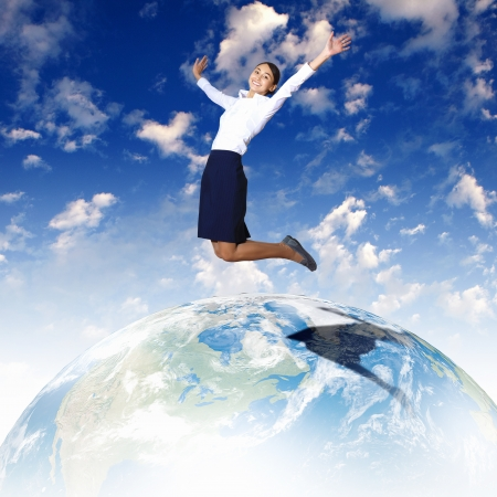 Business woman jumping up above the planet Earth photo
