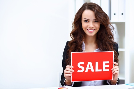 Young business woman with sale sign sitting at work place photo