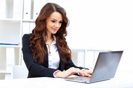 relaxed woman: Young pretty business woman with notebook in the office