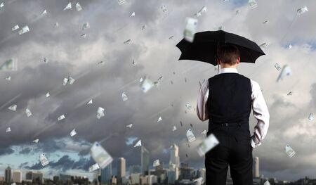 prognosis: Image of a business person standing under money rain with umbrella