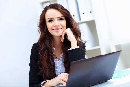 Giovane donna graziosa di affari con il taccuino in ufficio