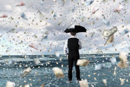 Young businessman standing with umbrella under money rain photo