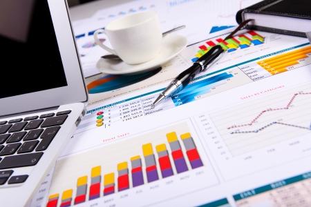 ganancias: Tablas y gr�ficos financieros de papel sobre la mesa