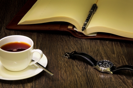 A cup of black coffee and a book photo