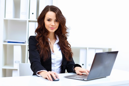thoughtful woman: Young pretty business woman with notebook in the office