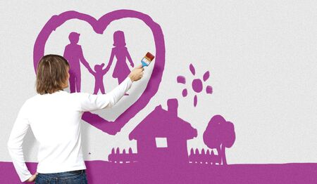 Young man with a paintbrush and family picture on the wall Stock Photo - 14731141