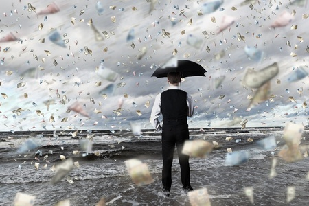 Image of a business person standing under money rain with umbrella Stock Photo - 14731101