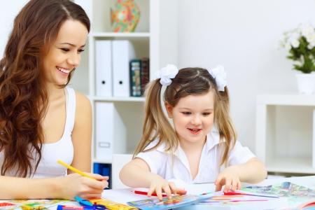 Jeune maman et petite fille �tudie � la maison