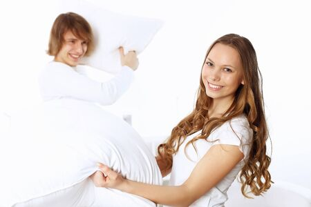 Young couple having fun with pillows at home photo