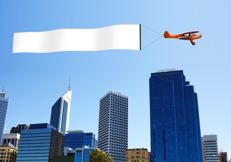 takeoff: Plane in the sky above the city with blank flag Stock Photo
