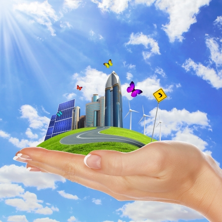ecological: Hands holding a green earth with solar batareis Stock Photo