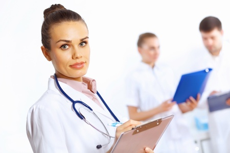 Young female doctor in white uniform with collegues on the background Stock Photo - 15185642