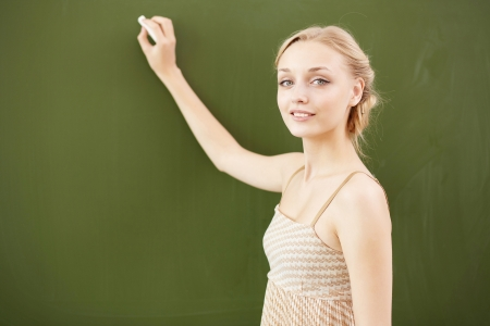 Young female teacher standing near blackboard at school Stock Photo