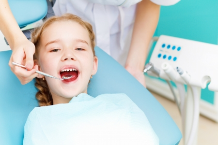 Little girl sitting in the dentists office photo
