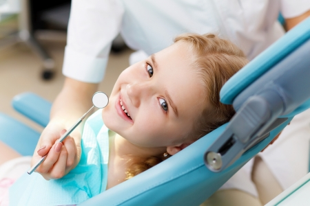 male dentist: Little girl sitting in the dentists office