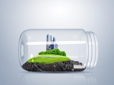 Ciudad verde en la colina en el interior de un frasco de vidrio