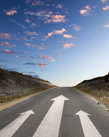 challenging mission: Image of road with white arrow directing forward Stock Photo