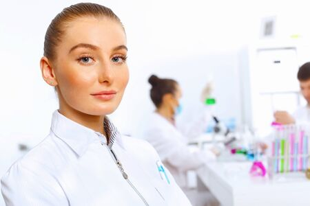 Young female doctor in white uniform with collegues on the background Stock Photo - 14888222