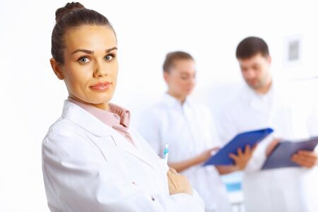 Young female doctor in white uniform with collegues on the background Stock Photo - 14888171