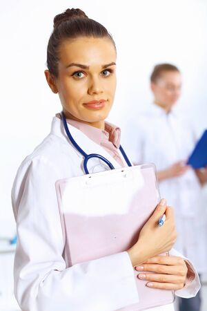 Young female doctor in white uniform with collegues on the background Stock Photo - 14888256