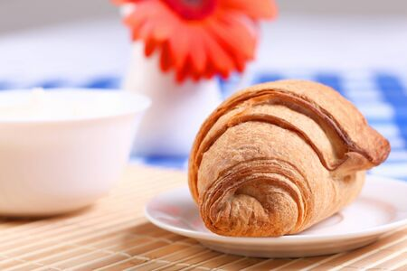 caf: Continental breakfast with croisant on white plate