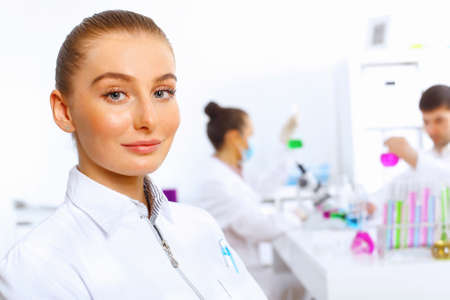 Young female doctor in white uniform with collegues on the background Stock Photo - 14888231
