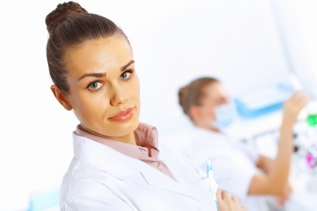 Young female doctor in white uniform with collegues on the background Stock Photo - 14888205