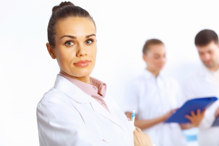 Young female doctor in white uniform with collegues on the background Stock Photo - 14888173