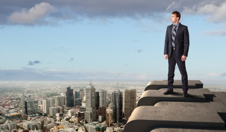 Business man standing high over a cityscape  photo