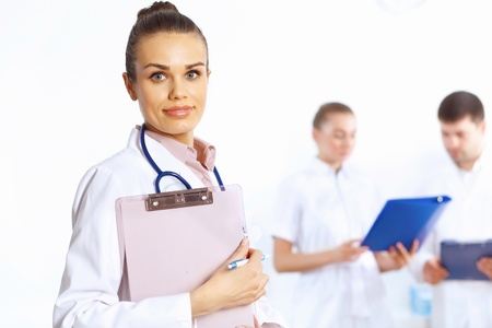 Young female doctor in white uniform with collegues on the background Stock Photo - 14888167