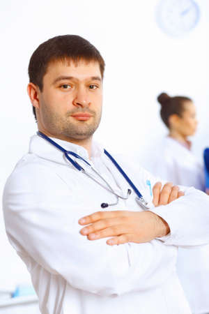 Young male doctor in white uniform with collegues on the background Stock Photo - 14888241
