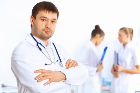 Young male doctor in white uniform with collegues on the background Stock Photo - 14888194