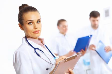 Young female doctor in white uniform with collegues on the background Stock Photo - 14888208