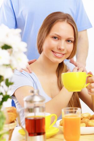 Beautiful young woman drinking tea from yellow cup photo