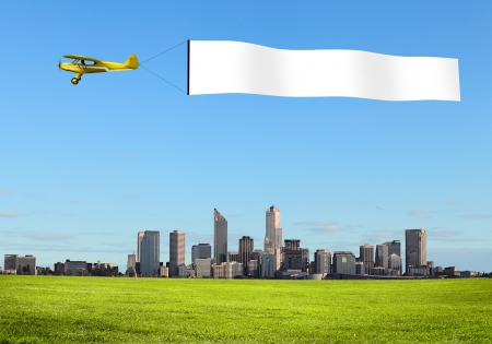Plane in the sky above the city with blank flag photo