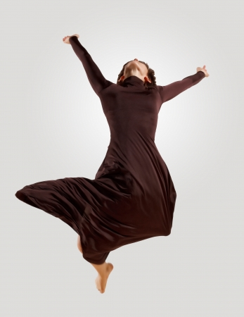 Girl dancing in a dark dress with a gray background  isolate photo