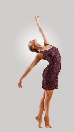 Girl dancing in a color dress with a gray background  isolate photo