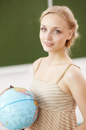 Young female teacher holding a globe at school photo