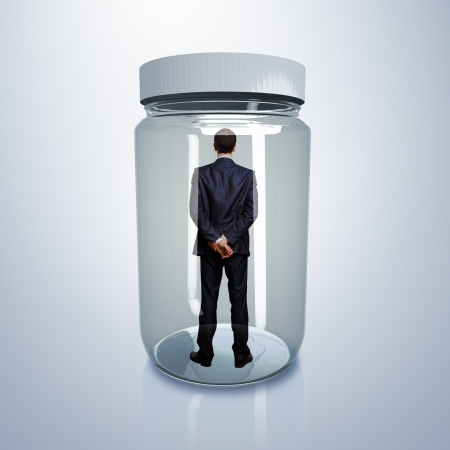 Businessman trapped inside a transparent glass jar Stock Photo - 15207512