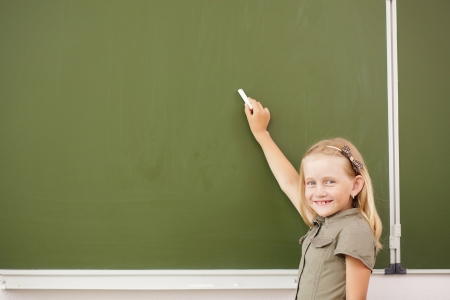 ni�os en la escuela: Scoolgirl de pie en clase cerca de la pizarra verde